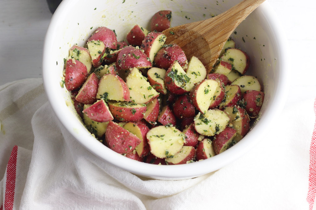 Ingredients mixed for parmesan pesto roasted potatoes