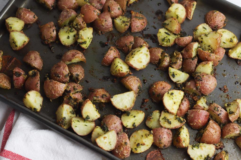 baked pesto potatoes on roasting pan